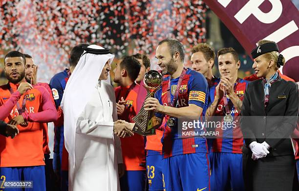 FC Barcelona's Andrés Iniesta holds a 18 carat gold cup which was presented to the team following a friendly football match between FC Barcelona and...