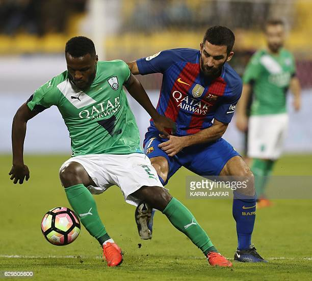 FC Barcelona's Arda Turan vies for the ball with AlAhly's Ali alZubaidi during a friendly football match between FC Barcelona and Saudi Arabia's...