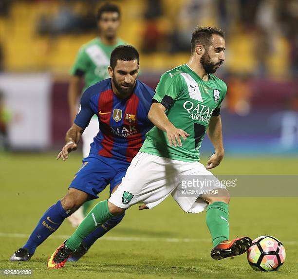 FC Barcelona's Arda Turan vies for the ball with AlAhly's Giannis Fetfatzidis during a friendly football match between FC Barcelona and Saudi...