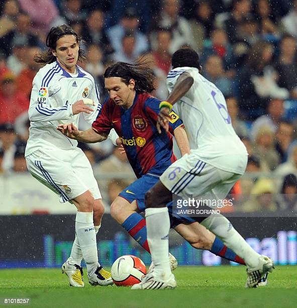 Barcelona's Argentine Lionel Messi vies wiyh Real Madrid's Fernando Gago and Mahamadou Diarra during a Spanish league football match at Santiago...