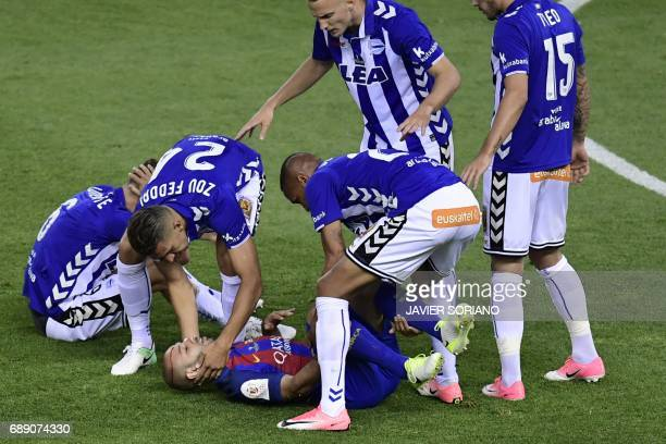 Barcelona's Argentinian defender Javier Mascherano is helped by Deportivo Alaves players after being injured during the Spanish Copa del Rey final...