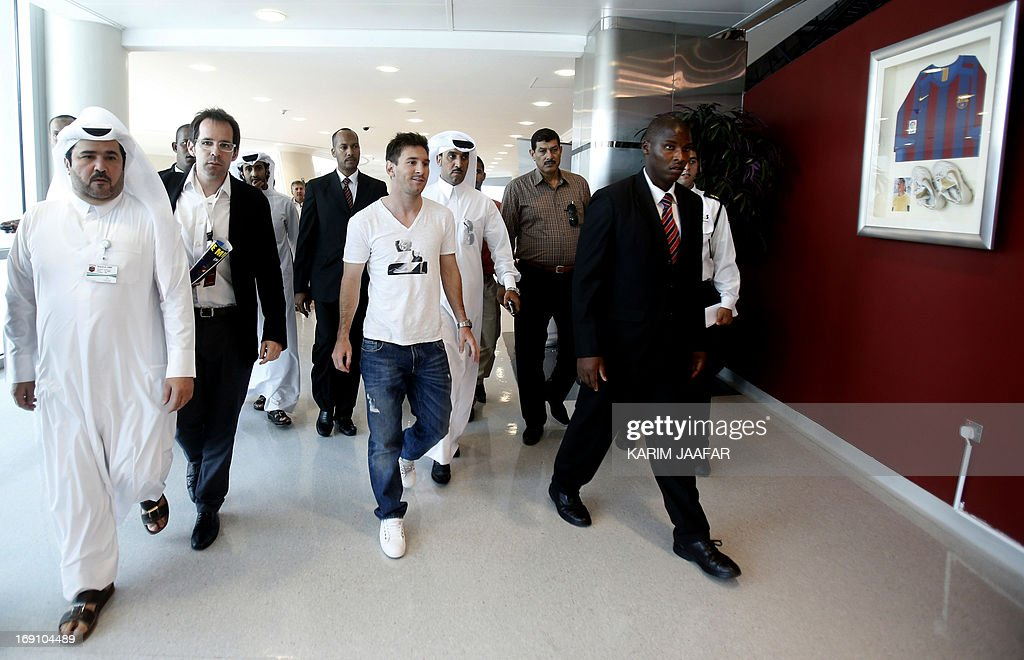 Barcelona's Argentinian football player Lionel Messi walks along a hall way following a press conference at the Aspire Academy of Sports Excellence, in Doha, on May 20, 2013. AFP PHOTO / AL-WATAN DOHA / KARIM JAAFAR == QATAR OUT ==