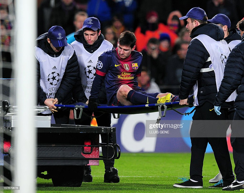 Barcelona's Argentinian forward Lionel leaves the pitch on a stretcher after being injured during the UEFA Champions League football match FC Barcelona vs SL Benfica at the Camp Nou stadium in Barcelona on December 5, 2012. AFP PHOTO / LLUIS GENE