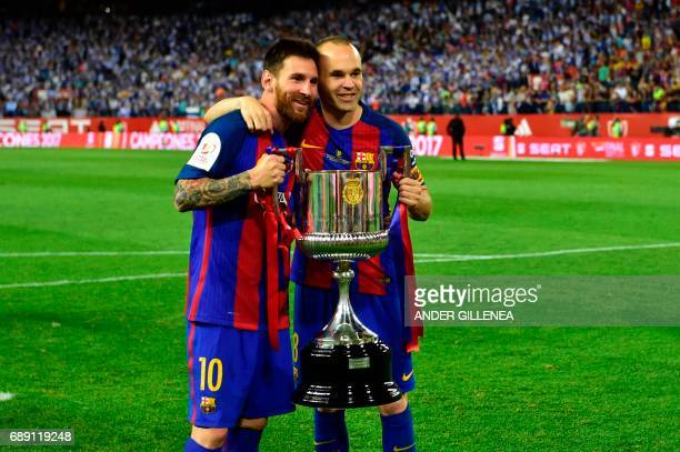 TOPSHOT Barcelona's Argentinian forward Lionel Messi and Barcelona's midfielder Andres Iniesta hold up the trophy after the team won the Spanish Copa...