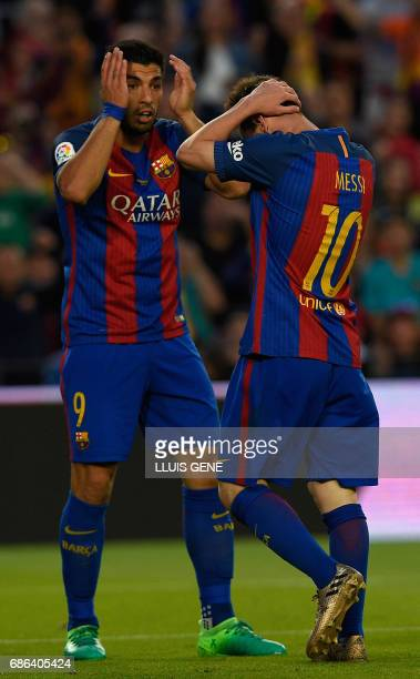 Barcelona's Argentinian forward Lionel Messi and Barcelona's Uruguayan forward Luis Suarez gesture during the Spanish league football match FC...