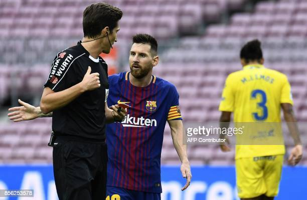 Barcelona's Argentinian forward Lionel Messi argues with referee Jose Luis Munuera Montero during the Spanish league football match FC Barcelona vs...