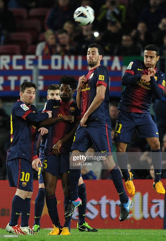 Barcelona's Argentinian forward Lionel Messi, Barcelona's Cameroonian midfielder Alex Song, Barcelona's midfielder Sergio Busquets and Barcelona's midfielder Thiago Alcantara form a wall to stop a free kick during the Spanish league football match FC Barcelona vs Rayo Vallecano at the Camp Nou stadium in Barcelona on March 17, 2013.