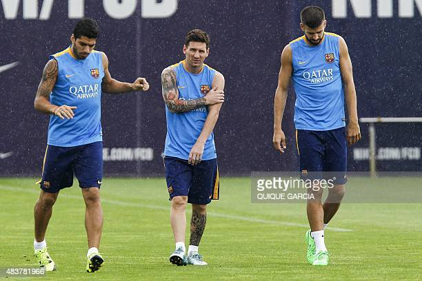 Barcelona's Argentinian forward Lionel Messi Barcelona's Uruguayan forward Luis Suarez and Barcelona's defender Gerard Pique take part in a training...