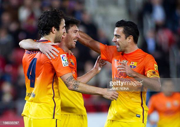Barcelona's Argentinian forward Lionel Messi celebrate with midfielder Xavi Hernandez and Cesc Fabregas after scoring during the Spanish league...