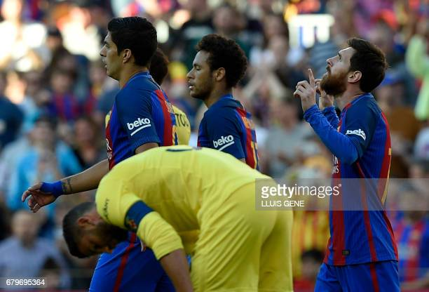 Barcelona's Argentinian forward Lionel Messi celebrates a goal beside Barcelona's Uruguayan forward Luis Suarez and Barcelona's Brazilian forward...