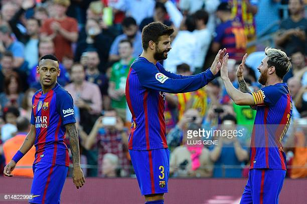 Barcelona's Argentinian forward Lionel Messi celebrates a goal with Barcelona's defender Gerard Pique as Barcelona's Brazilian forward Neymar looks...
