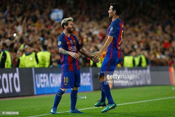Barcelona's Argentinian forward Lionel Messi celebrates a goal with Barcelona's midfielder Sergio Busquets during the UEFA Champions League football...