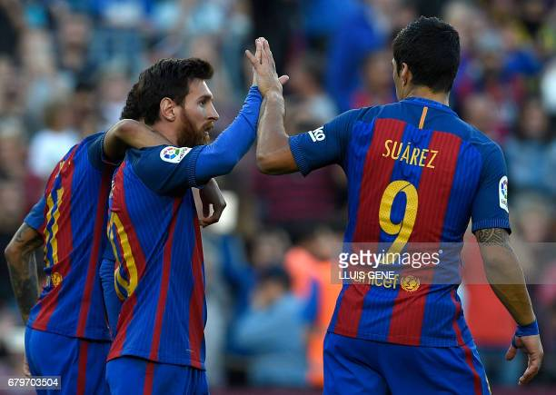 Barcelona's Argentinian forward Lionel Messi celebrates a goal with Barcelona's Uruguayan forward Luis Suarez and Barcelona's Brazilian forward...