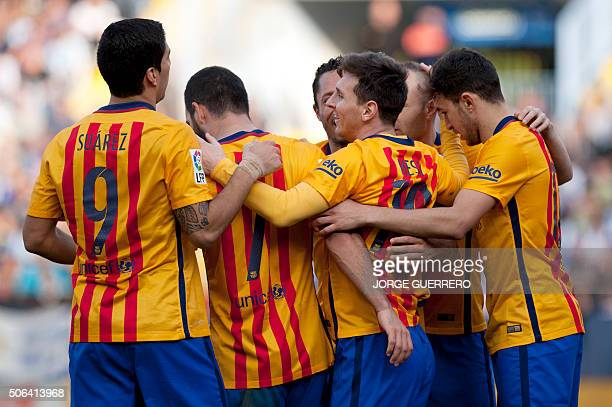 Barcelona's Argentinian forward Lionel Messi celebrates after scoring with teammates during the Spanish league football match Malaga CF vs FC...