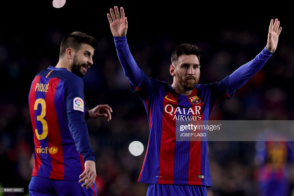 Barcelona's Argentinian forward Lionel Messi (R) celebrates his goal beside Barcelona's defender Gerard Pique during the Spanish league football match FC Barcelona vs RCD Espanyol at the Camp Nou stadium in Barcelona on December 18, 2016. / AFP / JOSEP