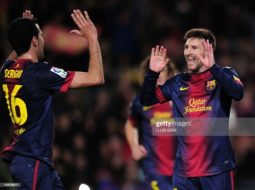 Barcelona's Argentinian forward Lionel Messi (R) celebrates with a teammate after scoring on a penalty kick during the Spanish league football match FC Barcelona vs RCD Espanyol at the Camp Nou stadium in Barcelona on January 6, 2013. AFP PHOTO/ LLUIS GENE