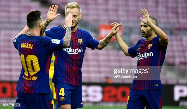 Barcelona's Argentinian forward Lionel Messi celebrates with Barcelona's Croatian midfielder Ivan Rakitic and Barcelona's Spanish midfielder Andres...