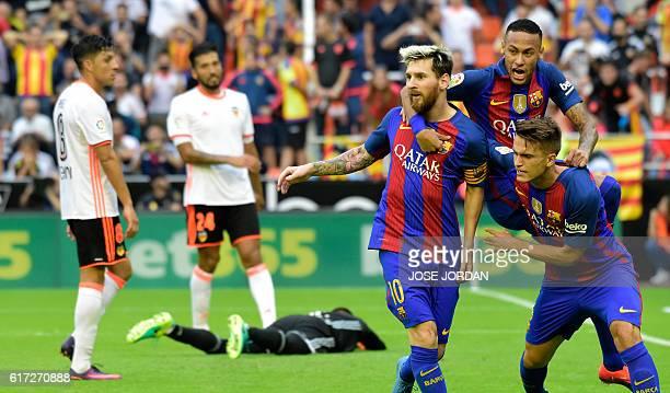 Barcelona's Argentinian forward Lionel Messi celebrates with Barcelona's Brazilian forward Neymar and Barcelona's midfielder Denis Suarez after...