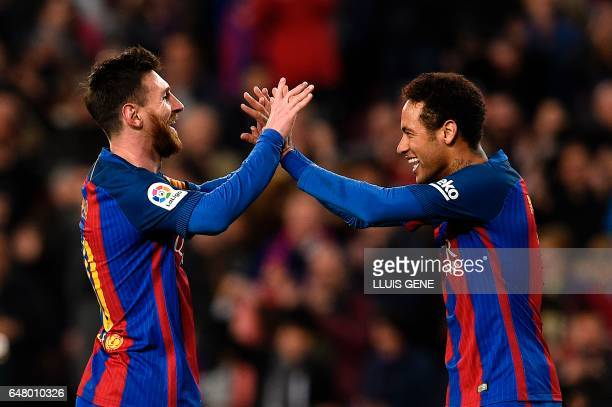 TOPSHOT Barcelona's Argentinian forward Lionel Messi celebrates with Barcelona's Brazilian forward Neymar after scoring a goal during the Spanish...