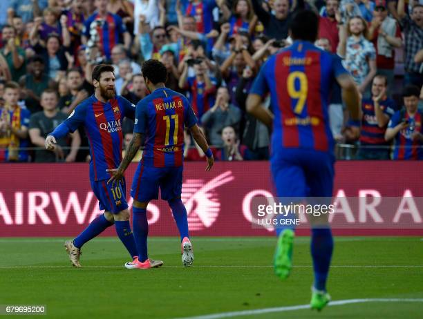 Barcelona's Argentinian forward Lionel Messi celebrates with Barcelona's Brazilian forward Neymar after scoring a goal during the Spanish league...