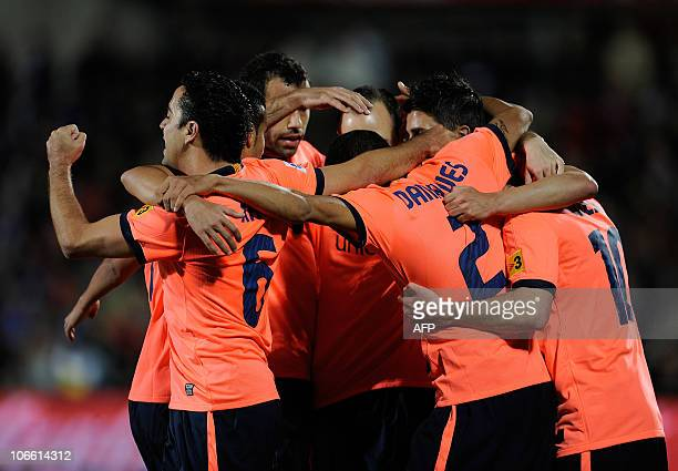 Barcelona's Argentinian forward Lionel Messi celebrates with his teammates after scoring against Getafe on November 7 2010 during their Spanish...