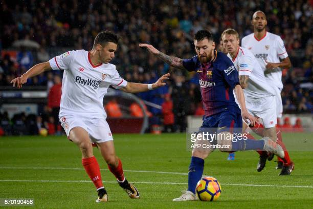 Barcelona's Argentinian forward Lionel Messi challenges Sevilla's French defender Sebastien Corchia during the Spanish league football match FC...