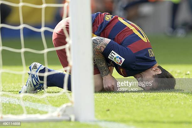 Barcelona's Argentinian forward Lionel Messi complains after being injured during the Spanish league football match FC Barcelona vs UD Las Palmas at...