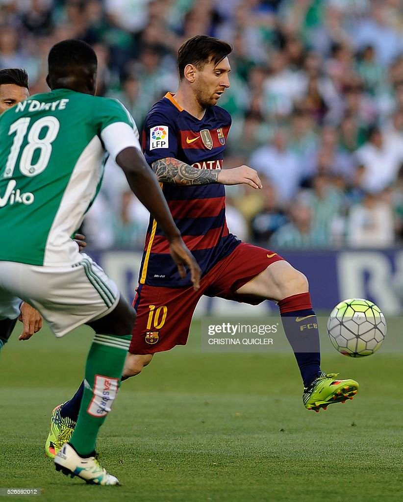 Barcelona's Argentinian forward Lionel Messi (R) controls the ball during the Spanish league football match Real Betis Balompie vs FC Barcelona at the Benito Villamarin stadium in Sevilla on April 30, 2016. / AFP / CRISTINA