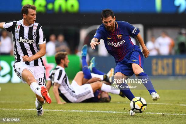 Barcelona's Argentinian forward Lionel Messi dodges past Juventus midfielder from Venezuela Tomas Rincon during the International Champions Cup match...