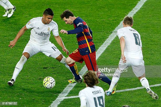Barcelona's Argentinian forward Lionel Messi dribbles the ball in front of Real Madrid's Brazilian midfielder Casemiro during the Spanish league...