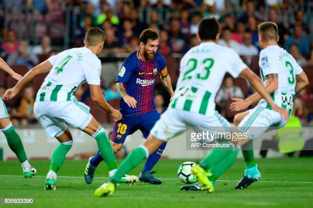 Barcelona's Argentinian forward Lionel Messi faces several Betis players during the Spanish league footbal match FC Barcelona vs Real Betis at the...