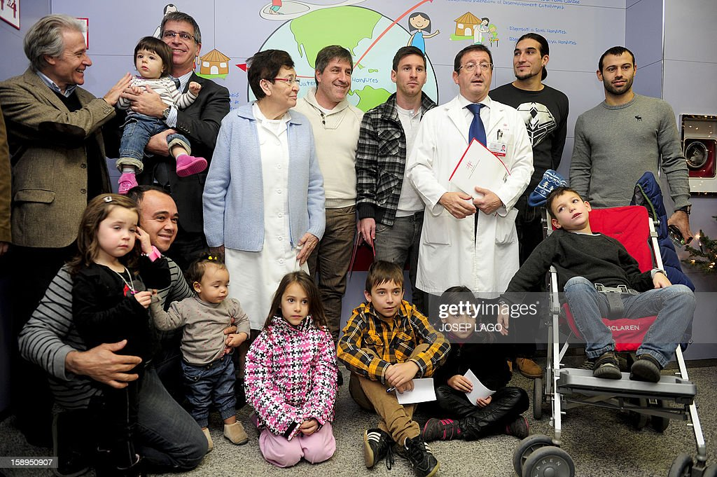 Barcelona's Argentinian forward Lionel Messi (4th R), goalkeeper Jose Manuel Pinto (2nd R) and Argentinian midfielder Javier Mascherano (R) pose with doctors and childen during a visit to the Hospital de Nens (the Children's Hospital) in Barcelona on January 4, 2013.