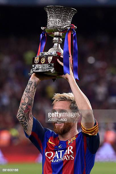 Barcelona's Argentinian forward Lionel Messi holds the Spanish Supercup trophy after winning the second leg of the Spanish Supercup football match...