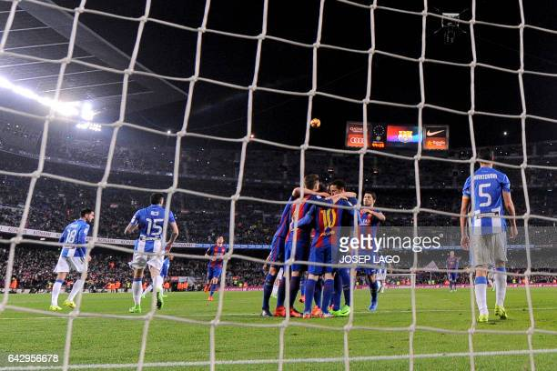 Barcelona's Argentinian forward Lionel Messi is congratulated by teammates after scoring from a penalty during the Spanish league football match FC...