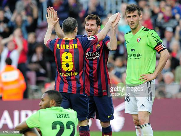 Barcelona's Argentinian forward Lionel Messi is congratulated by his teammate Barcelona's midfielder Andres Iniesta after scoring during the Spanish...