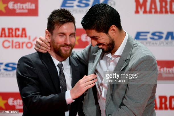 Barcelona's Argentinian forward Lionel Messi is congratulated by his teammate Barcelona's Uruguayan forward Luis Suarez after receiving the 2017...