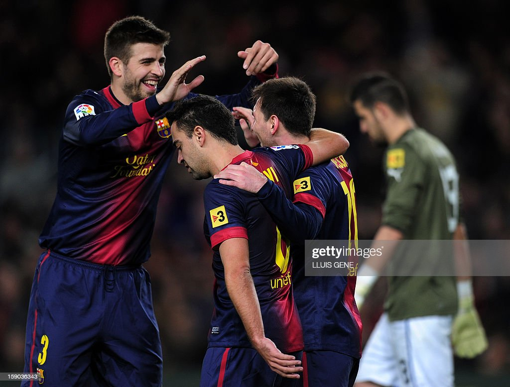 Barcelona's Argentinian forward Lionel Messi (R) is congratulated by Barcelona's defender Gerard Pique (L) and Barcelona's midfielder Xavi Hernandez (C) after scoring on a penalty kick during the Spanish league football match FC Barcelona vs RCD Espanyol at the Camp Nou stadium in Barcelona on January 6, 2013.