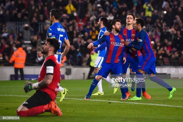 Barcelona's Argentinian forward Lionel Messi is congratulated by teammates Barcelona's Brazilian forward Neymar and Barcelona's midfielder Denis...