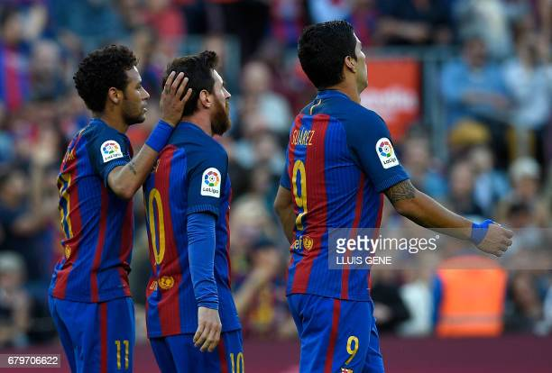 Barcelona's Argentinian forward Lionel Messi is congratulated by Barcelona's Brazilian forward Neymar beside Barcelona's Uruguayan forward Luis...