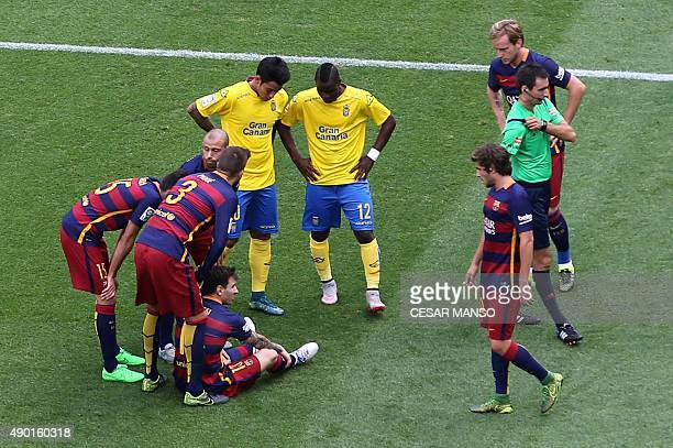 Barcelona's Argentinian forward Lionel Messi is surrounded by other players after being injured during the Spanish league football match FC Barcelona...