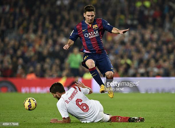 Barcelona's Argentinian forward Lionel Messi jumps over Sevilla's Portuguese midfielder Daniel Carrico during the Spanish league football match FC...