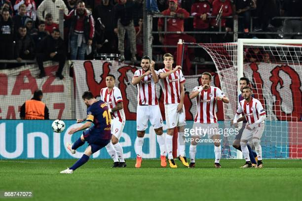 Barcelona's Argentinian forward Lionel Messi kicks the ball in front of Olympiakos players during the UEFA Champions League group D football match...