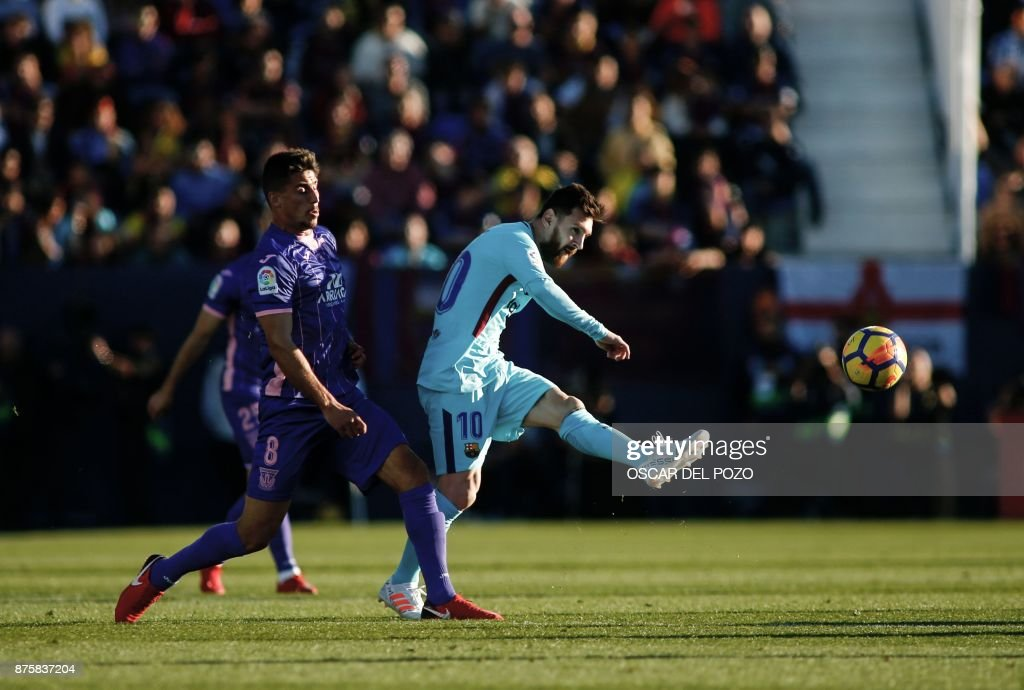 Barcelona's Argentinian forward Lionel Messi (R) kicks the ball past Leganes' Brazilian midfielder Gabriel Appelt during the Spanish league football match Leganes vs Barcelona at the Butarque stadium in Leganes on November 18, 2017. /