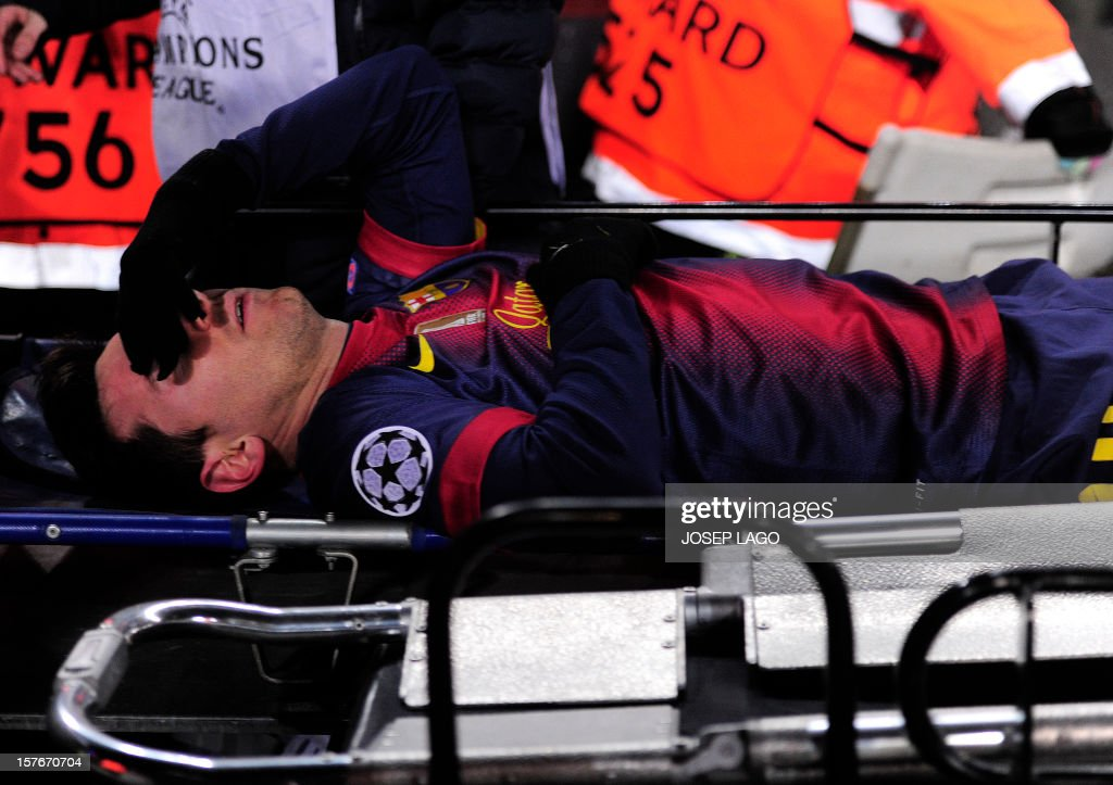 Barcelona's Argentinian forward Lionel Messi leaves the pitch on a stretcher after being injured during the UEFA Champions League football match FC Barcelona vs SL Benfica at the Camp Nou stadium in Barcelona on December 5, 2012. AFP PHOTO / JOSEP LAGO