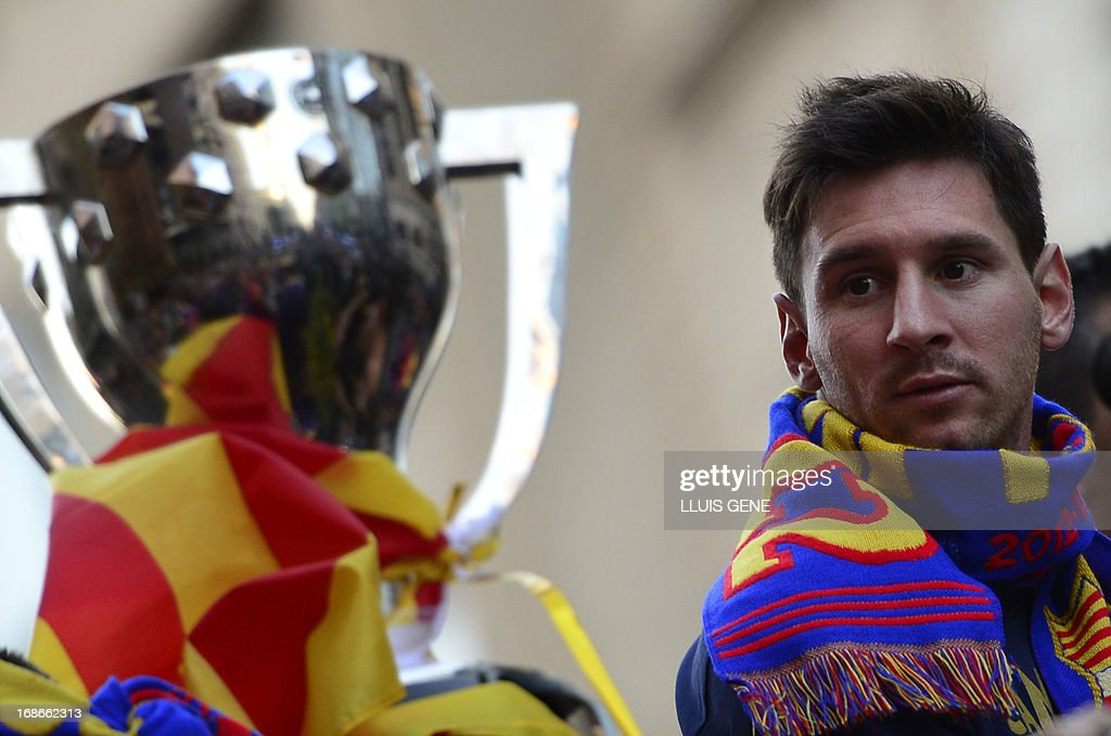 Barcelona's Argentinian forward Lionel Messi looks at the cup as he and his teammates parade on a bus through a crowd of supporters celebrating in the streets of Barcelona on May 13, 2013, two days after their team won the Spanish league. The Catalans didn't even need to set foot on the pitch to seal the title on May 11 as Real Madrid's 1-1 draw with Espanyol meant Barca had already been crowned champions before their 2-1 win over Atletico Madrid on May 12, 2013.