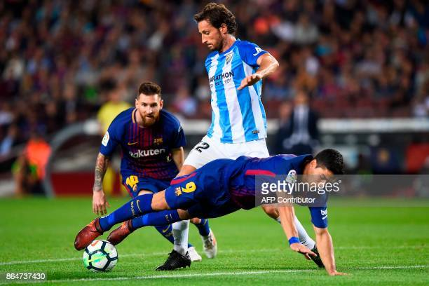 Barcelona's Argentinian forward Lionel Messi observes as Malaga's French defender Paul Baysse challenges Barcelona's Uruguayan forward Luis Suarez...