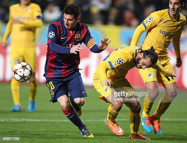 Barcelona's Argentinian forward Lionel Messi passes the ball ahead of Apoel's Cypriot midfielder Stathis Aloneftis during their UEFA Champions League...