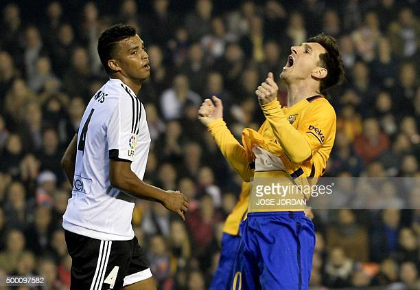 Barcelona's Argentinian forward Lionel Messi reacts after missing an attempt on goal next to Valencia's Brazilian defender Aderlan Santos during the...