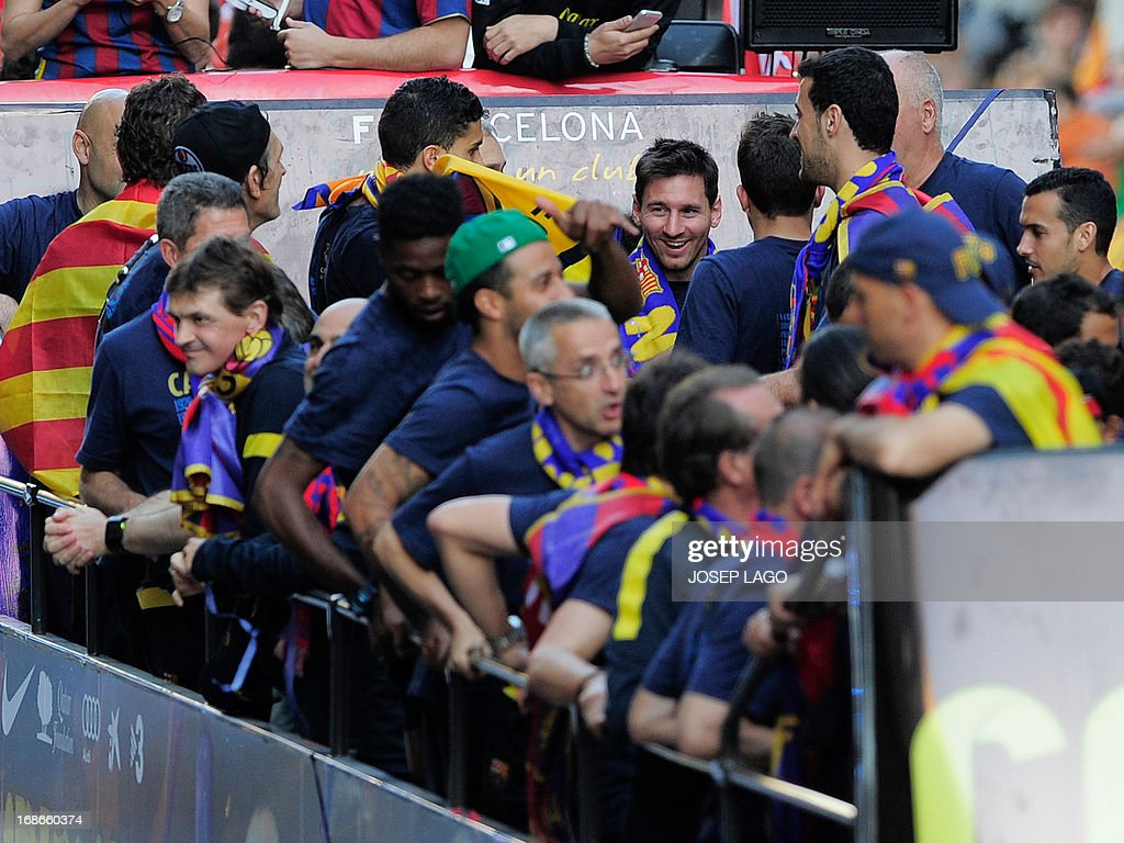 Barcelona's Argentinian forward Lionel Messi (C) reacts as he and his teammates parade on a bus through a crowd of celebrating supporters in the streets of Barcelona on May 13, 2013, two days after their team won the Spanish league. The Catalans didn't even need to set foot on the pitch to seal the title on May 11 as Real Madrid's 1-1 draw with Espanyol meant Barca had already been crowned champions before their 2-1 win over Atletico Madrid on May 12, 2013.