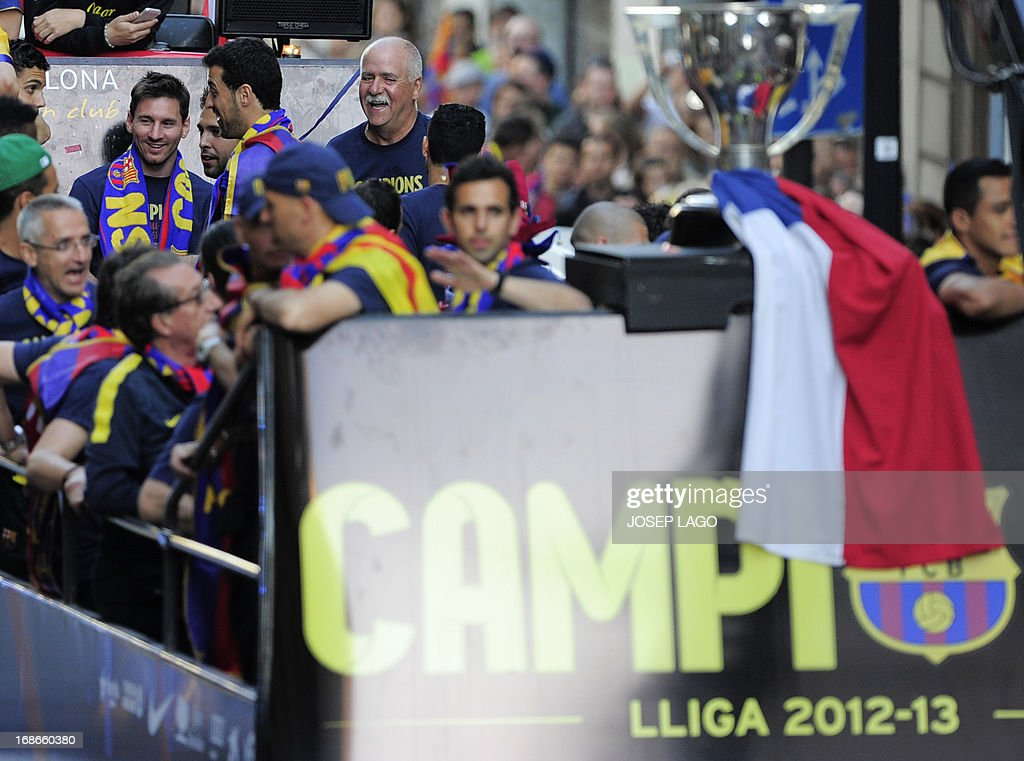 Barcelona's Argentinian forward Lionel Messi (L) reacts as he and his teammates parade on a bus through a crowd of celebrating supporters in the streets of Barcelona on May 13, 2013, two days after their team won the Spanish league. The Catalans didn't even need to set foot on the pitch to seal the title on May 11 as Real Madrid's 1-1 draw with Espanyol meant Barca had already been crowned champions before their 2-1 win over Atletico Madrid on May 12, 2013.